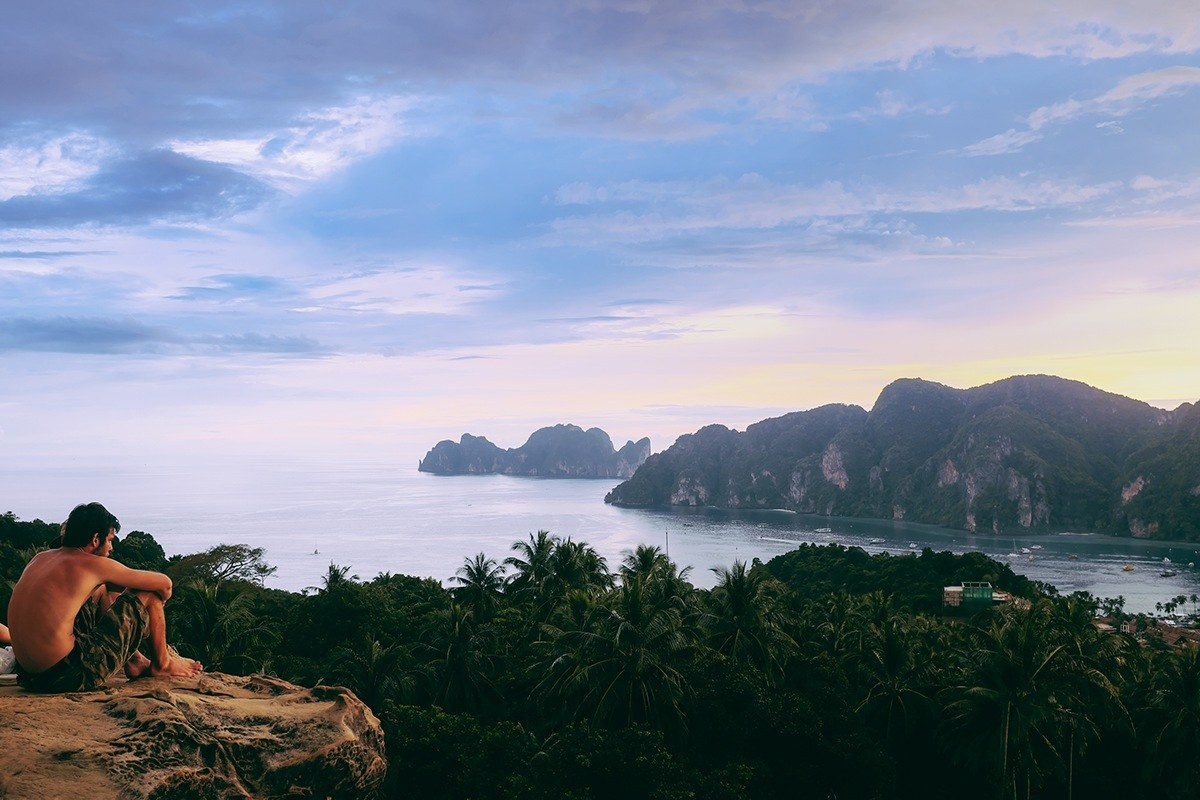 Sitting on the edge of a cliff in Thailand taking it all in backpacking the asian trail