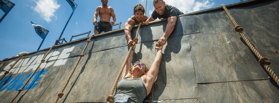 Savage Race team leading a helping hand up the wall
