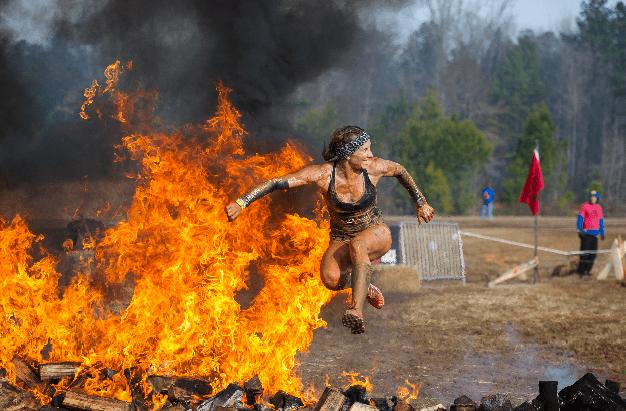 Spartan Race girl jumping over fire