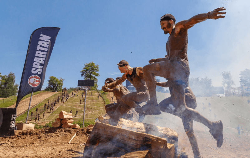 Spartan Race men jumping over obstacle