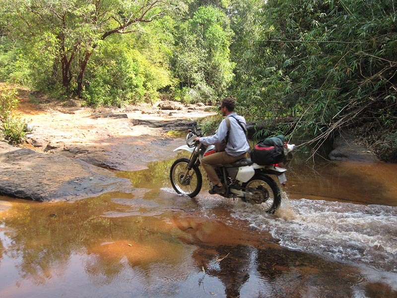 Motorcycling through Cambodia past a river