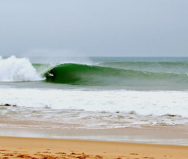 Surfer getting barrelled at Supertubos best surf beaches in Portugal