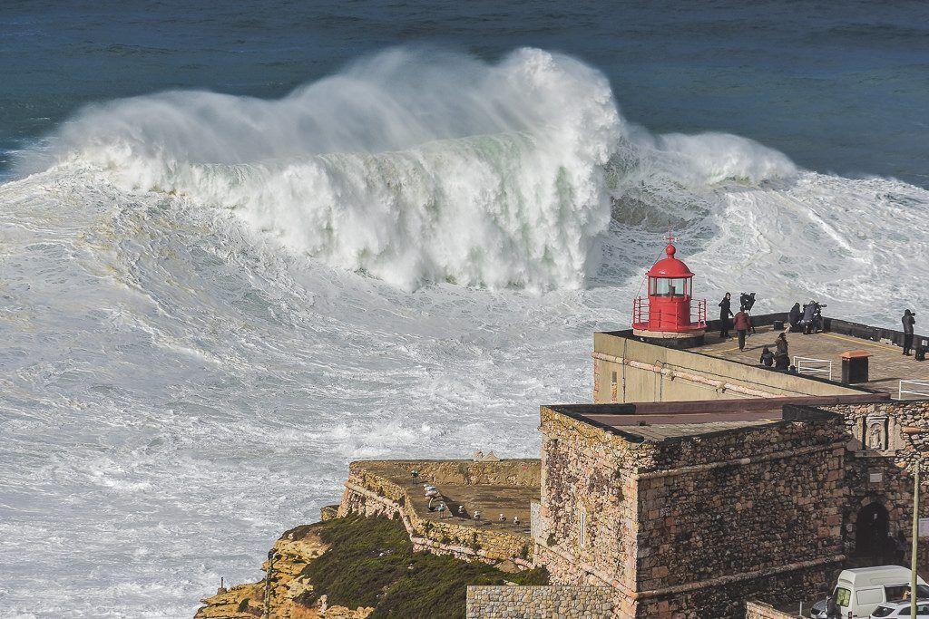 Waves crashing into Nazaré lighthouse