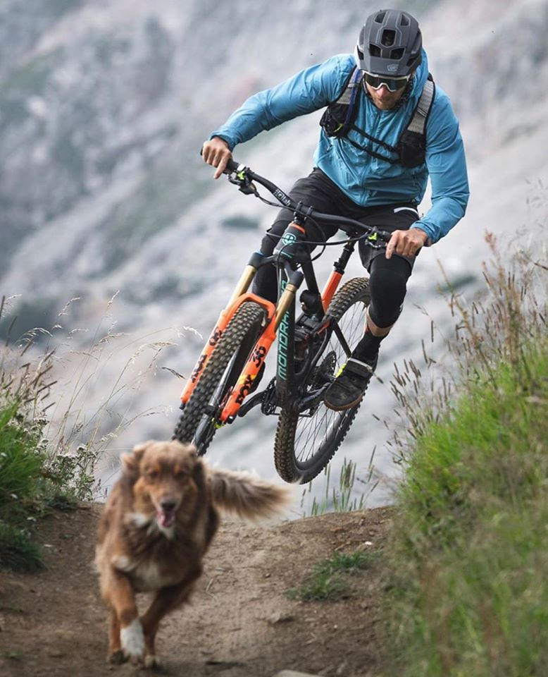 mountain biker chasing his dog on the trails
