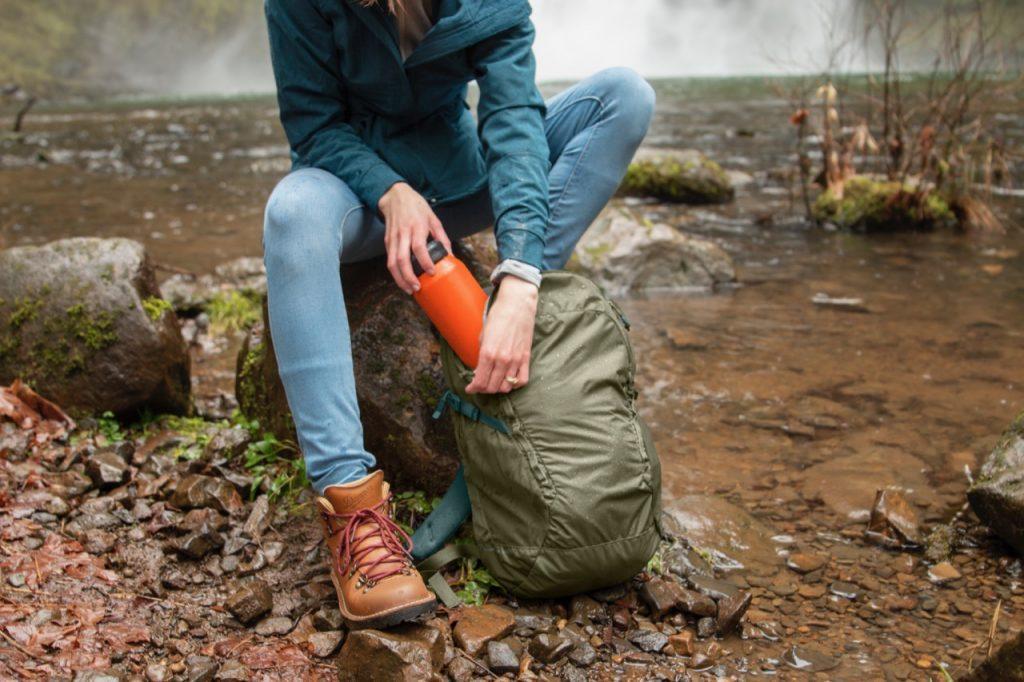 hiker loading water bottle into her backpack